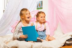 Two little smiling pixies reading the fairy-tale Stock Photos