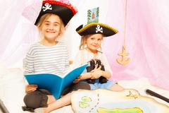 Two cute girls playing pirates, reading fairy-tale - stock photo