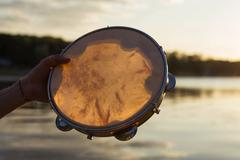 Musical instrument tambourine or pandeiro on a background of the sky at sunset Stock Photos