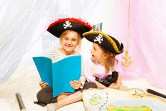 Happy girls reading book about pirate's treasures Stock Photos