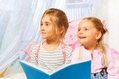 Little beautiful pixies reading the fairy-tale - stock photo