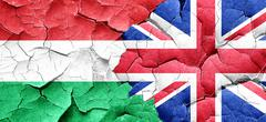 Hungary flag with Great Britain flag on a grunge cracked wall - stock illustration