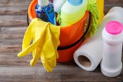 Plastic bucket with cleaning supplies on wood background - stock photo