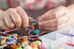Woman making home craft art bijouterie Stock Photos