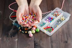 Beautiful hands with colored beads Stock Photos