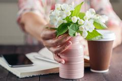 Woman work at table with flowers bouquet ana take away coffee Stock Photos