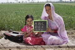 Portrait of mother and daughter holding a writing slate with alphabets written Stock Photos
