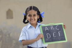 Portrait of a cheerful girl in school uniform holding a slate Stock Photos