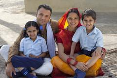 Portrait of a happy Indian family sitting on cot Stock Photos