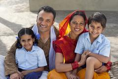 Portrait of a happy Indian family of four sitting on cot Stock Photos