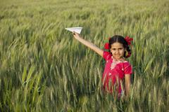 Portrait of little girl playing with a paper aero plane in wheat field Stock Photos
