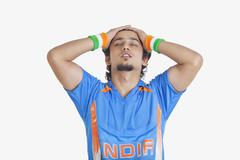 Displeased young man in Indian cricket team jersey standing with hands on head Stock Photos