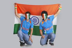 Two male friends with face painted in a tricolor holding Indian flag over Stock Photos