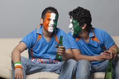 Male friends with face painted in Indian tricolor having drink while sitting on Stock Photos