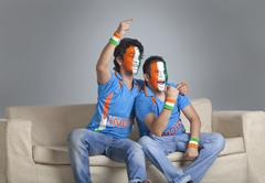 Happy male friends with face painted in Indian tricolor cheering while sitting Stock Photos