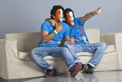 Full length of excited male friends with face painted in Indian tricolor sitting Stock Photos