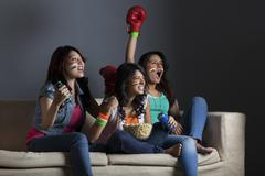 Enthusiastic young female friends watching boxing match together at home Stock Photos