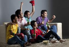 Enthusiastic male friends watching boxing match together at home Stock Photos