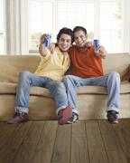 Portrait of happy young male friends holding tin cans while sitting comfortably Stock Photos