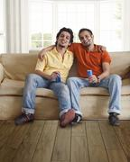 Portrait of happy young male friends sitting comfortably on sofa with tin cans Stock Photos