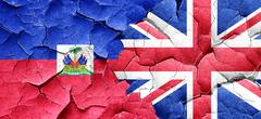 Haiti flag with Great Britain flag on a grunge cracked wall - stock illustration