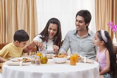Happy Indian family having pizza together at restaurant Stock Photos