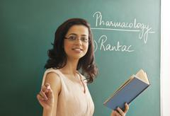 Portrait of young female teacher holding chalk and book against green board Stock Photos