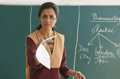 Portrait of an angry female teacher holding paper against chalkboard Kuvituskuvat