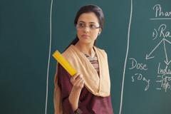 An angry young female teacher holding ruler against chalkboard Kuvituskuvat