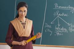 Portrait of young female teacher with attitude holding ruler against chalkboard Stock Photos