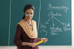 Portrait of an angry female lecturer holding ruler against green board Kuvituskuvat