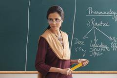 An angry female lecturer holding ruler against green board Stock Photos