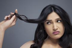 Young woman twisting hair finger over colored background Stock Photos