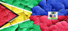 Guyana flag with Haiti flag on a grunge cracked wall Stock Illustration