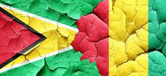 Guyana flag with Guinea flag on a grunge cracked wall Stock Illustration