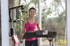 Portrait of happy young woman smiling while exercising on a treadmill Stock Photos