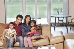 Portrait of happy Indian family of four sitting together on sofa Stock Photos
