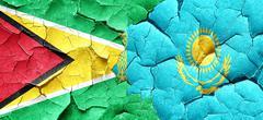 Guyana flag with Kazakhstan flag on a grunge cracked wall - stock illustration