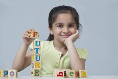 Portrait of little girl stacking blocks isolated over blue background Stock Photos