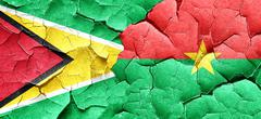 Guyana flag with Burkina Faso flag on a grunge cracked wall - stock illustration