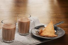 Glasses of chai on newspaper with plate of samosa over a wooden surface Stock Photos
