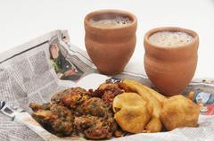 Indian pakoras , bhajiyas and fried potato balls with chai in traditional cup Stock Photos