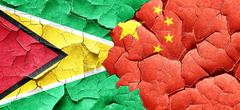 Guyana flag with China flag on a grunge cracked wall Stock Illustration