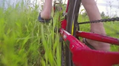 Slow motion man on red bike rides through the tall grass - stock footage