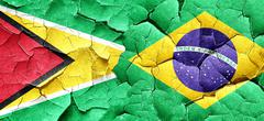 Guyana flag with Brazil flag on a grunge cracked wall - stock illustration