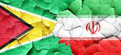 Guyana flag with Iran flag on a grunge cracked wall Stock Illustration