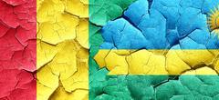 Guinea flag with rwanda flag on a grunge cracked wall - stock illustration