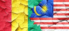 Guinea flag with Malaysia flag on a grunge cracked wall - stock illustration