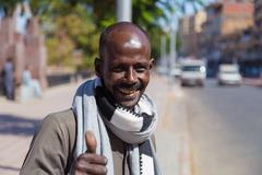ASWAN, EGYPT - FEBRUARY 6, 2016: Portrait of smiling local man showing thumbs - stock photo