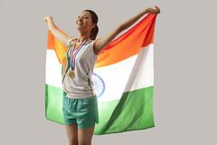 Female medalist celebrating victory with Indian flag isolated over gray Stock Photos
